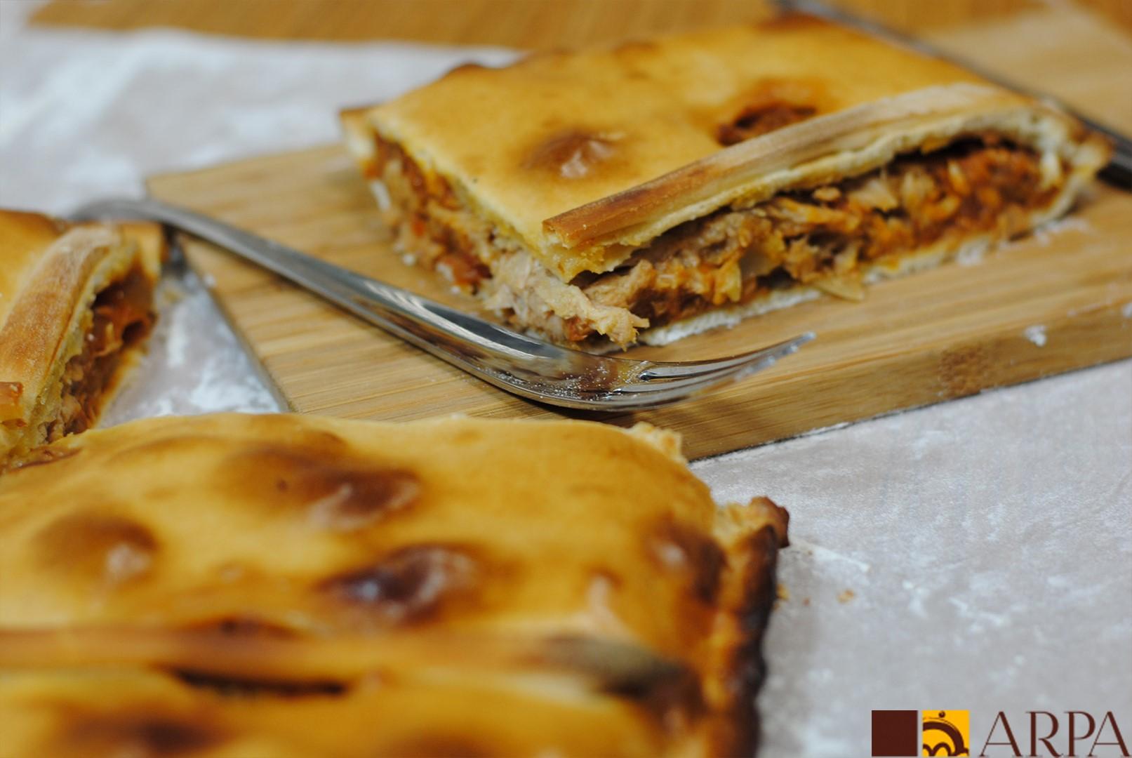 Empanada de atún, elaborada con masa de pan y rellena de pisto de tomate y verduras y atún