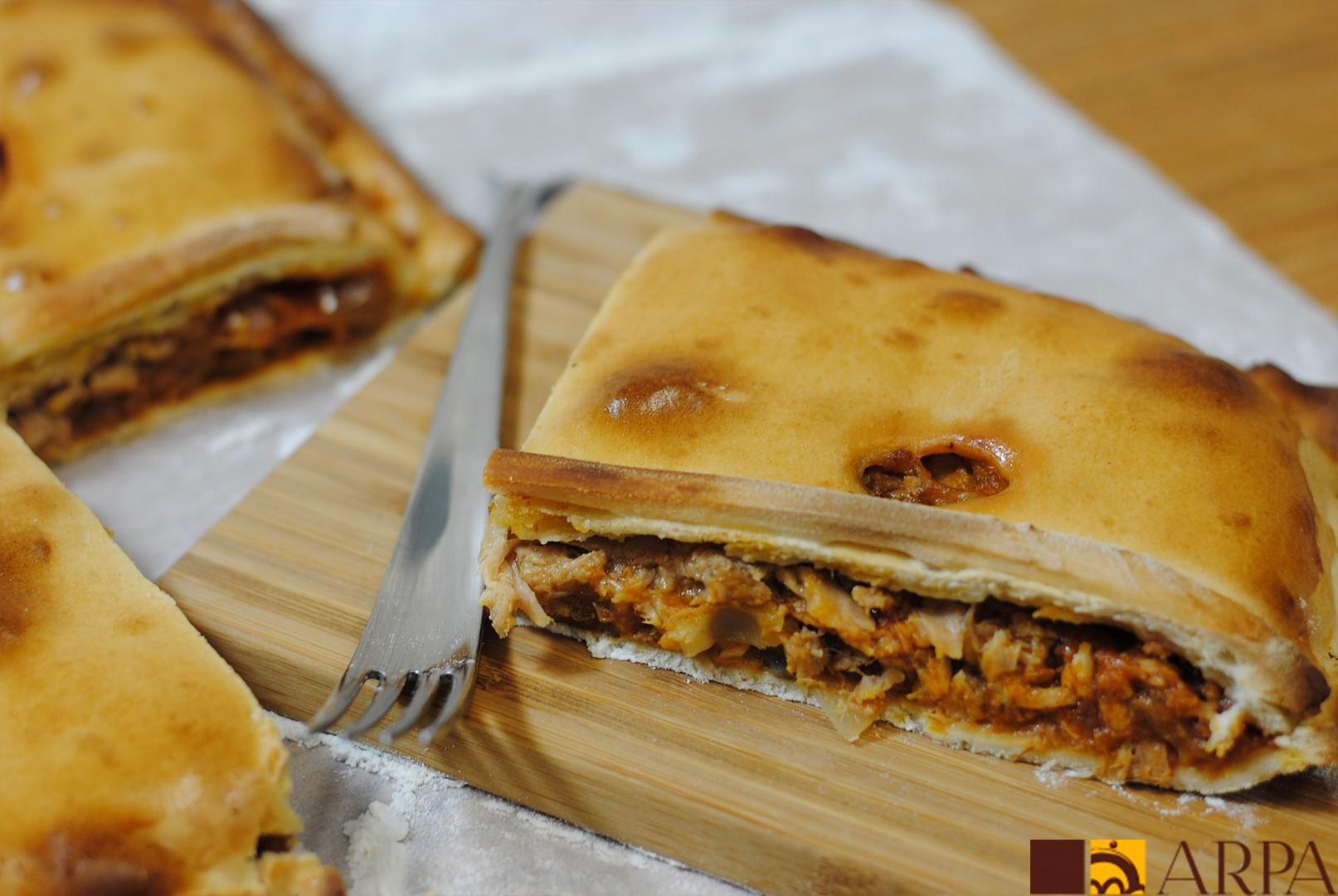 Empanada cuadrada fabricada manualmente con masa pan y rellena de pisto de tomate y verduras y carne