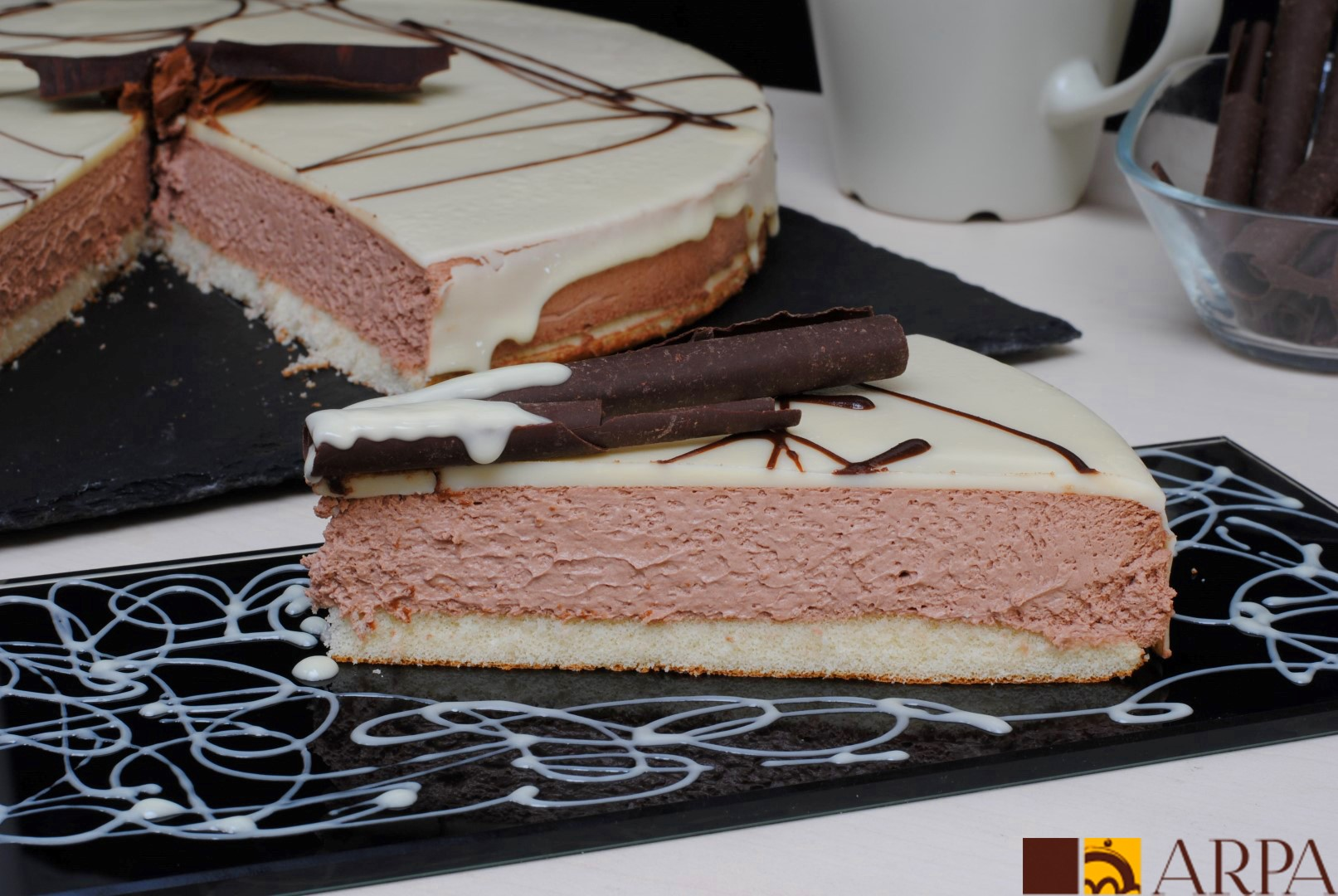 Mousse de bombón, interior de chocolate negro y bañado con una capa de chocolate blanco