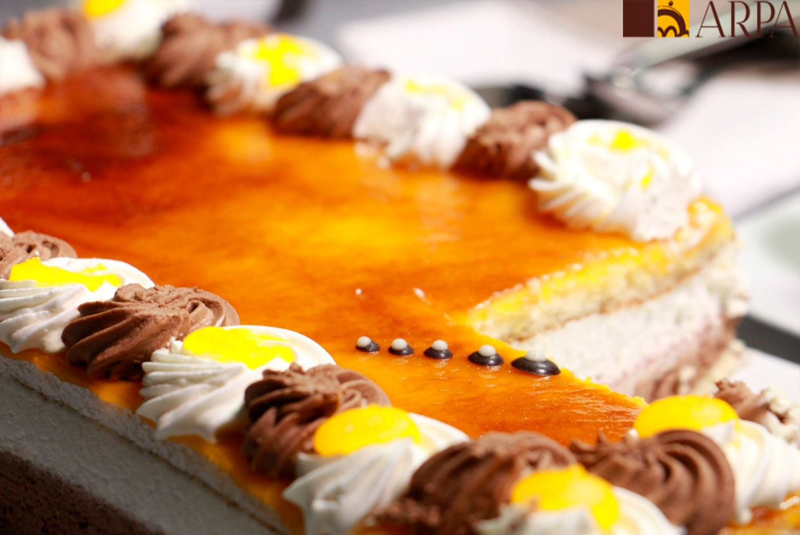 Pastel relleno de una capa de nata y una de trufa recubierto de yema de huevo quemada con azúcar y decorado con nata y trufa