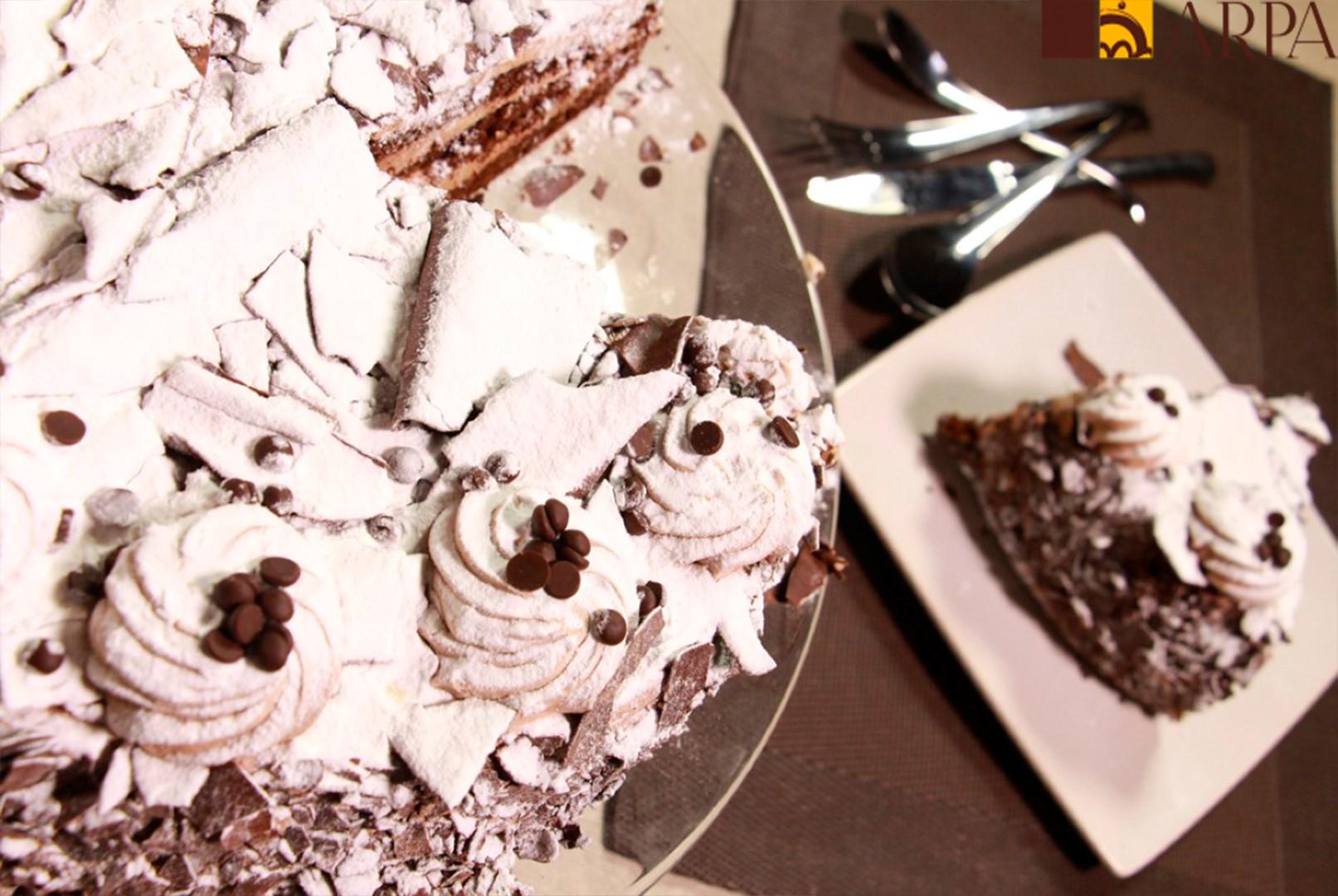 Pastel de bizcocho de chocolate relleno de mantequilla chocolateada y recubierto de virutas de chocolate negro y espolvoreada con azúcar glass