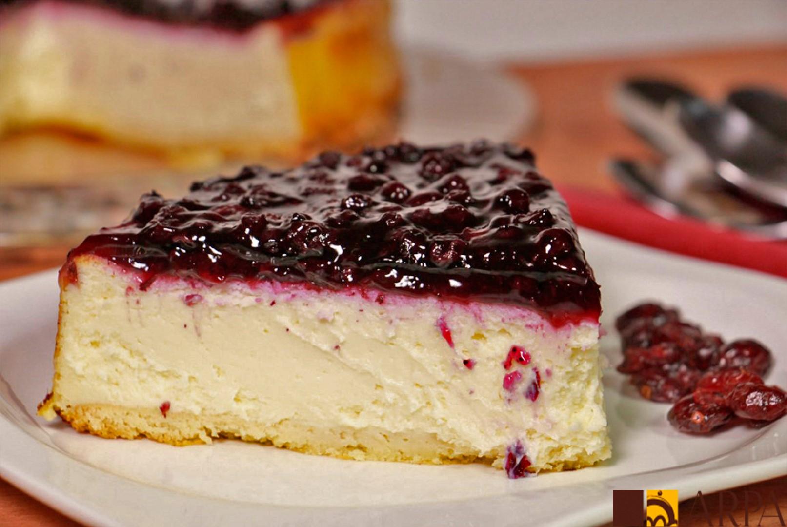 Pastel de queso crema recubierto con mermelada de arándanos negros