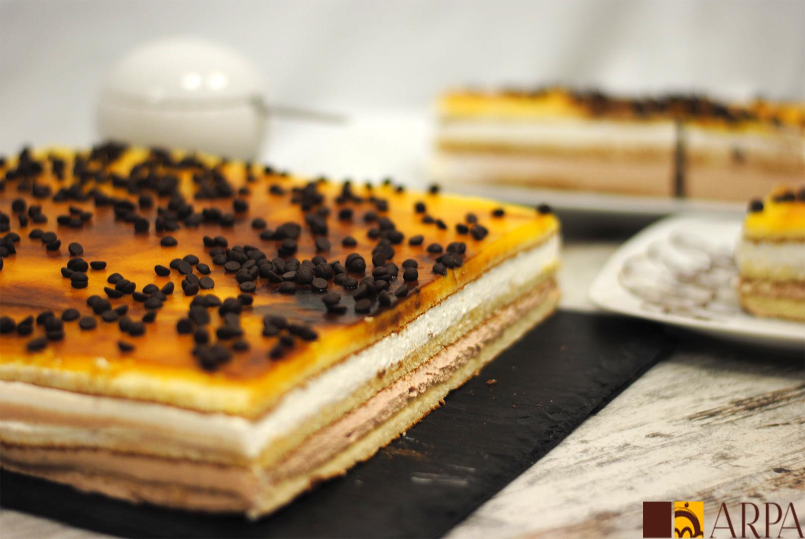 Pastel rectangular relleno de una capa de trufa y una de nata, recubierto por yema y decorado con perlas de chocolate negro
