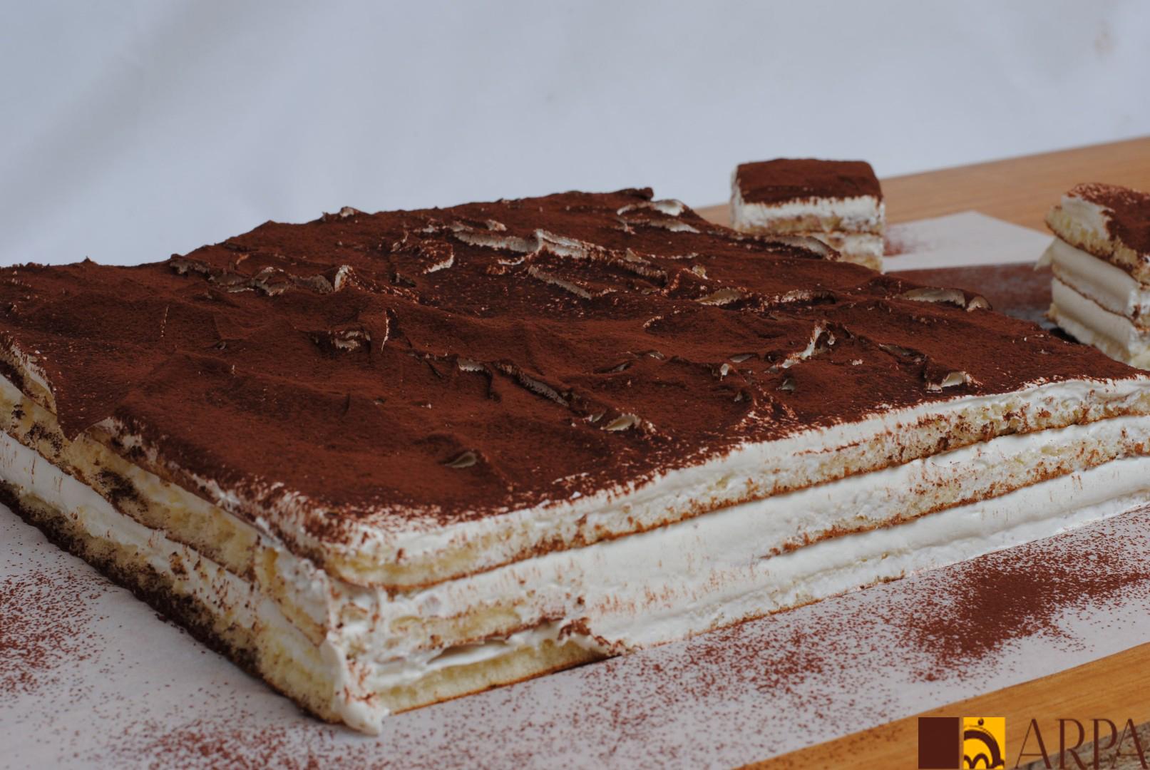 Plancha de tiramisú espolvoreada con cacao en polvo entera y cortada