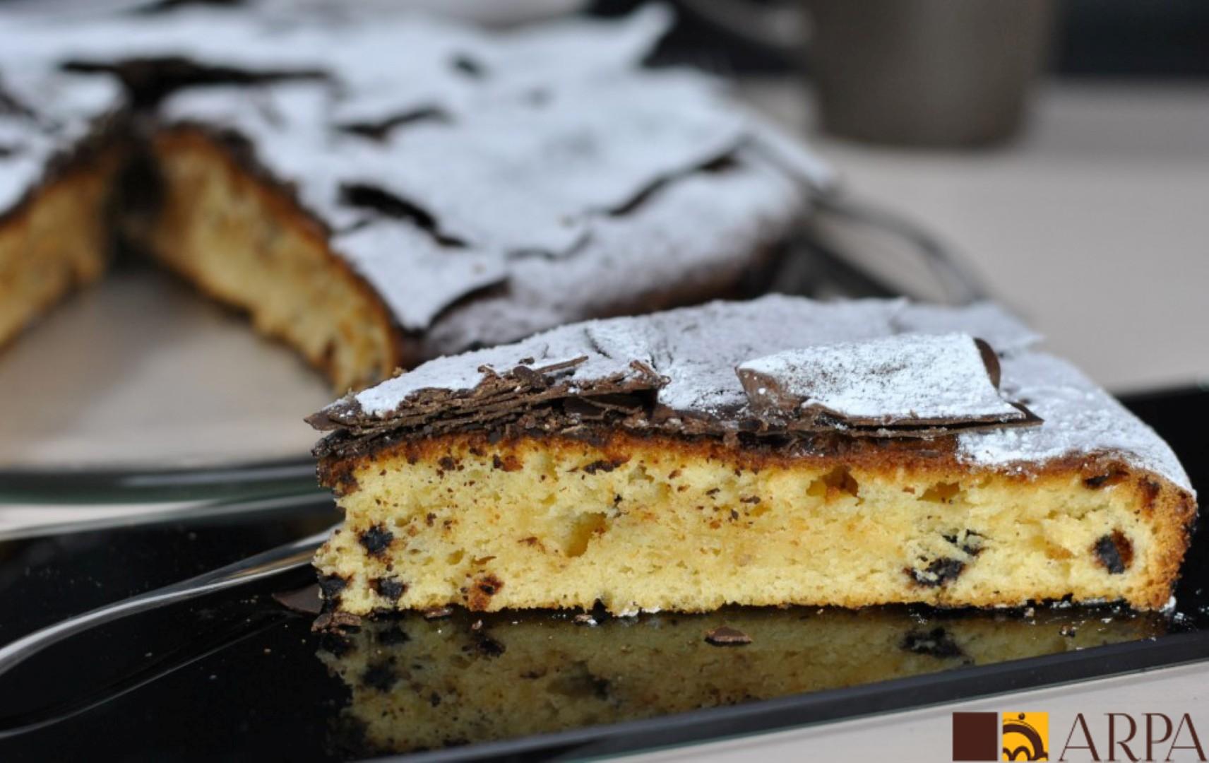 Tarta de bizcocho con perlas de chocolate cubierto de láminas de chocolate y azúcar glass